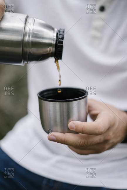 Man pouring coffee from an insulated container