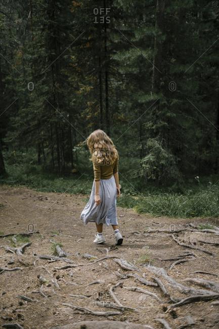 Krasnoyarsk, Russia - July 29, 2017: Blonde woman walking in forest from behind