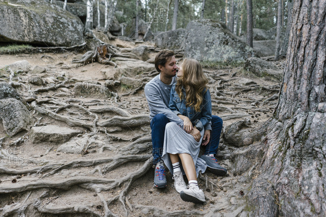Couple kissing while sitting together in a forest