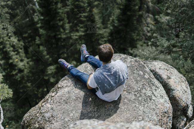 Man sitting on rocky mountain ledge