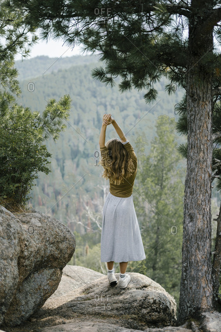 Rear view of blonde woman stretching on rocky mountain ledge