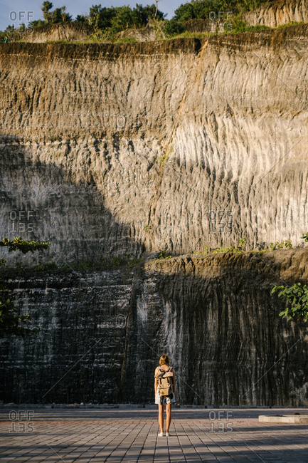 Back view of woman looking at rock wall outside