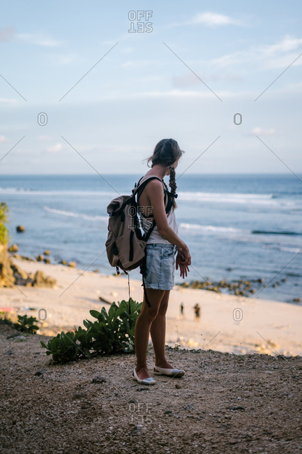 Backpacking female traveler watching beachgoers from hilltop in the shade