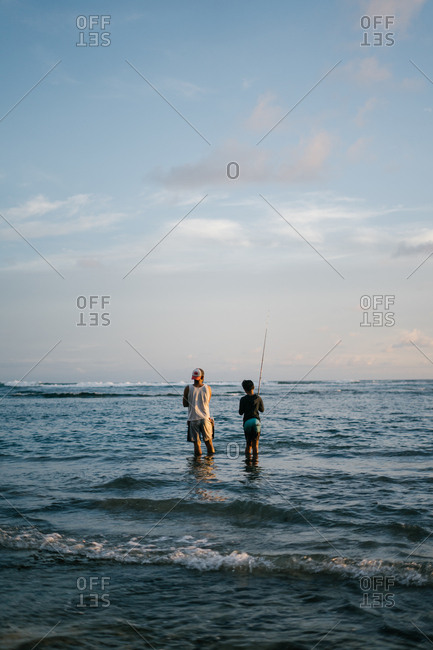 Two young vacationers fishing in shallow ocean