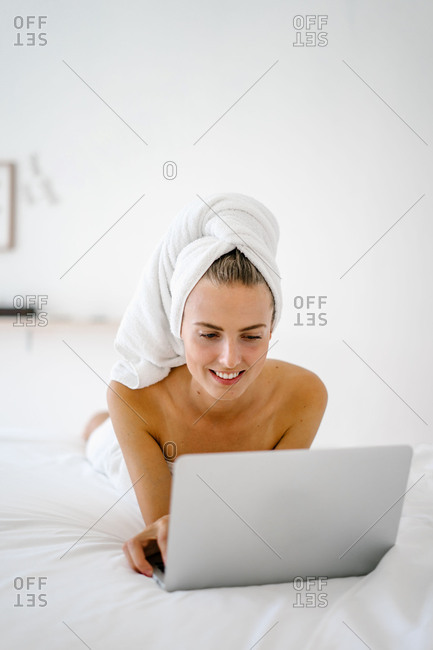 Woman working on laptop in bath towel on bed