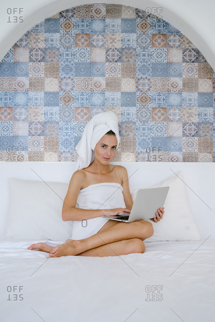 Woman in bath towel looking at camera in bedroom with computer