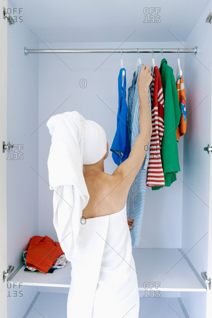 Woman picking out clothes in closet in bath towel
