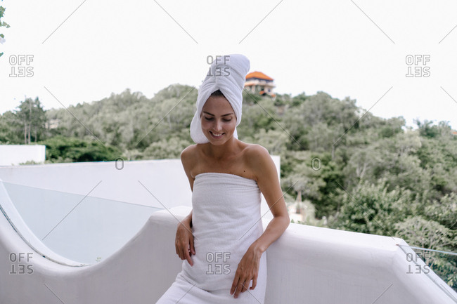 Female vacationer leaning on hotel balcony after shower