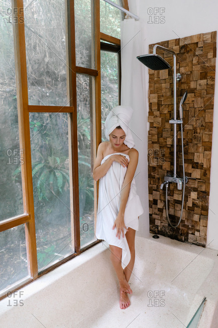 Woman leaning against glass shower wall looking down in bath towel