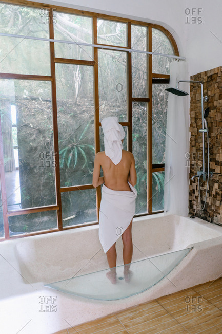 Woman looking outside of resort bathroom in the shower