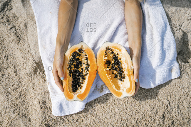 Hands holding exotic fruit on sunny beach towel