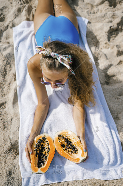 Woman lying on towel at the beach with fresh fruit