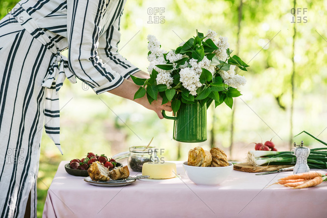 Woman placing a bunch of freshly picked lilacs on table for brunch