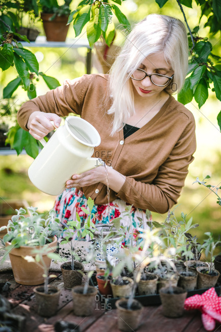 Woman pouring water into a planter