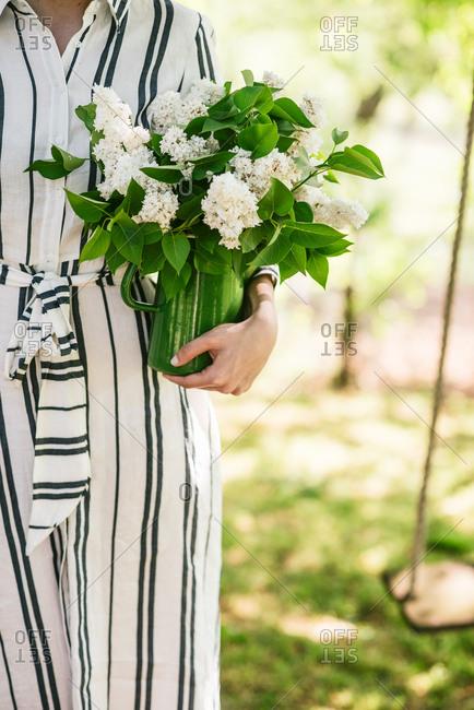 Woman wearing striped dress holding vase of fresh flowers in sunny garden
