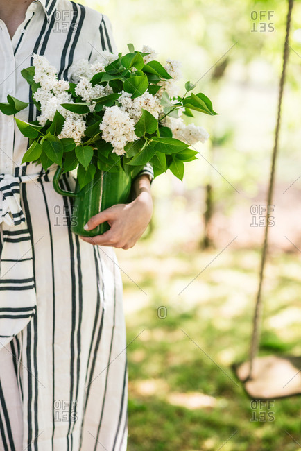 Close up of woman in sunny garden wearing striped dress holding vase of fresh picked flowers