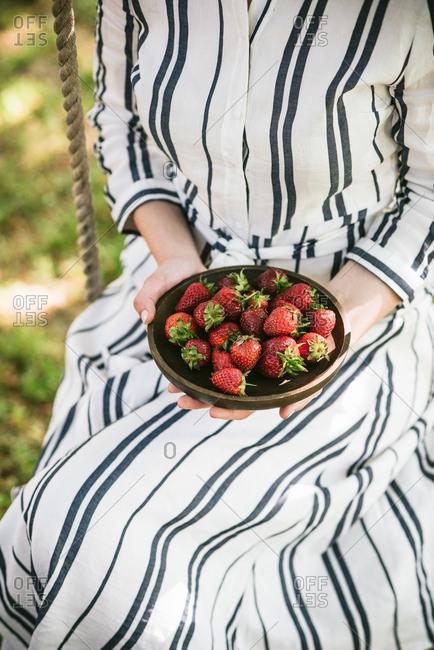 Woman wearing striped dress sitting on garden swing holding bowl of ripe strawberries