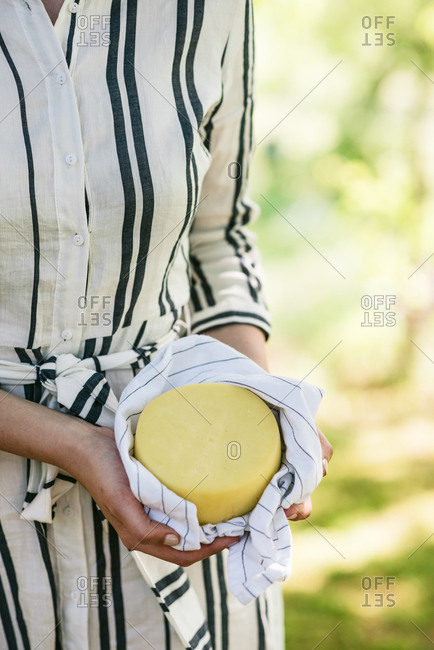 Woman in striped dress standing in spring garden holding wheel of cheese in tea towel