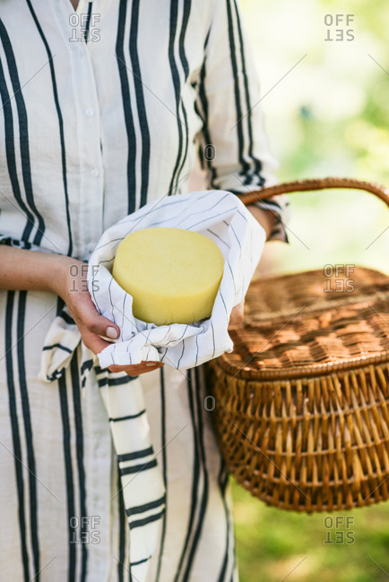 Woman in striped dress holding wheel of cheese and picnic basket in spring garden setting