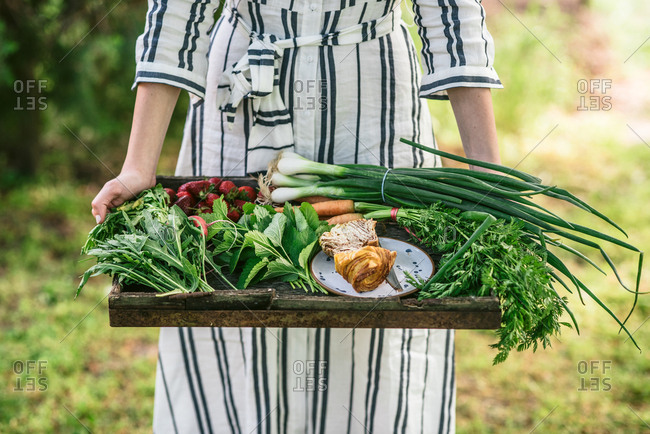 Woman in striped dress presenting tray of seasonal spring produce from the garden