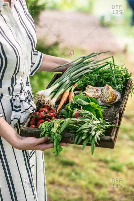 Side view of woman standing in garden holding tray of fresh spring produce
