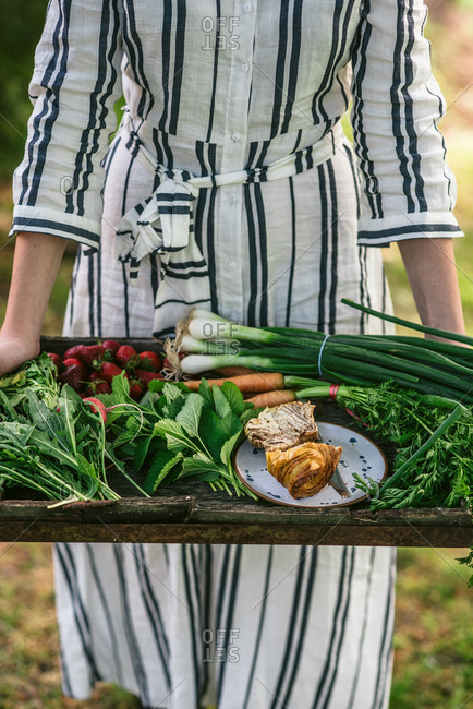 Cropped view of woman holding wooden tray of seasonal spring produce from the garden