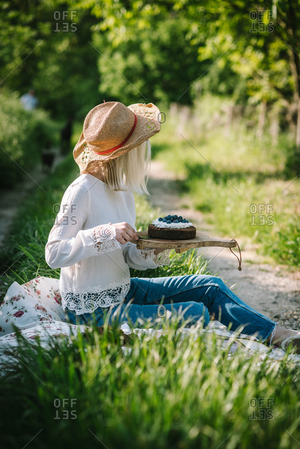 Woman sitting in field with head turned away serving piece of cake from wooden board