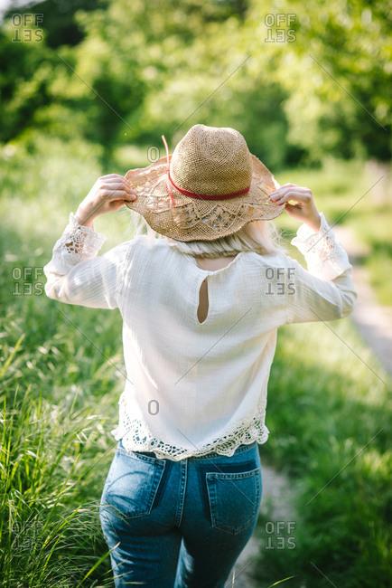 Rearview of woman walking in field holding hat brim