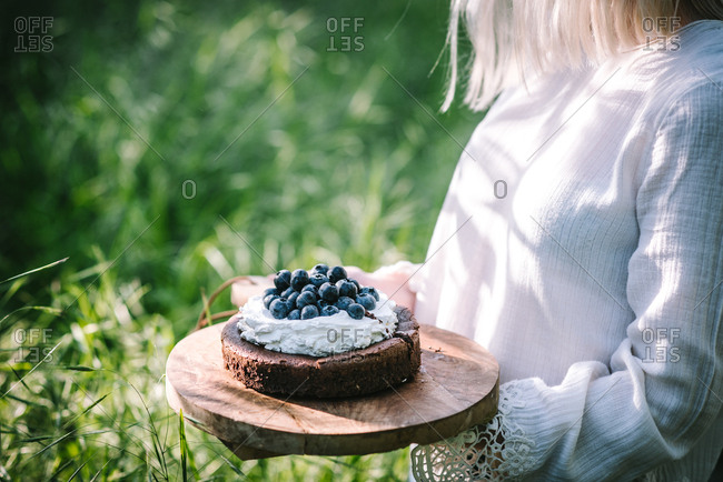 Woman standing in field holding a chocolate cake topped with blueberries and whipped cream