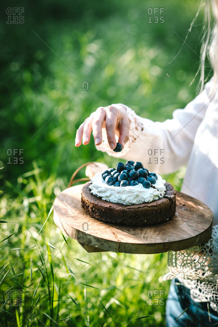 Woman standing in field picking berry off chocolate cake topped with blueberries and whipped cream