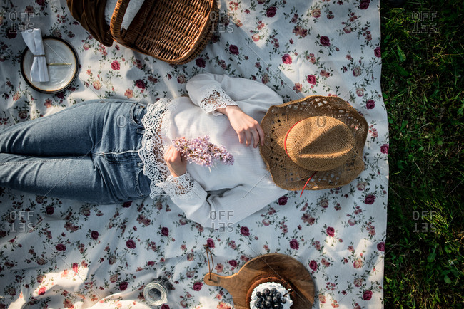 Overhead view of woman taking a nap during picnic with hat covering her face