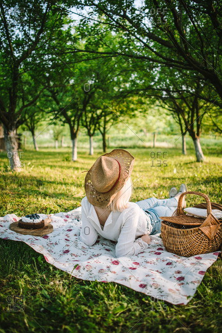 Rearview of woman lounging on picnic blanket in orchard on beautiful spring afternoon