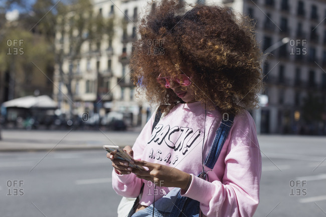 Beautiful and stylish black woman using mobile phone. Barcelona, Spain.
