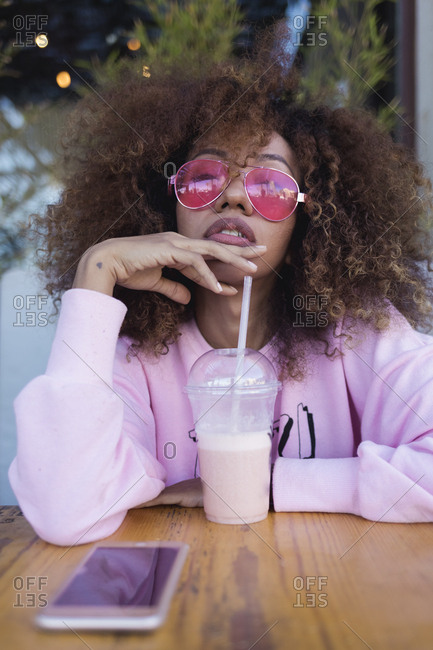 Stylish Curly Black Woman portraits out of a bar, drinking a juice.  Barcelona, Spain.