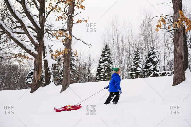 Young boy outside on sled in the winter