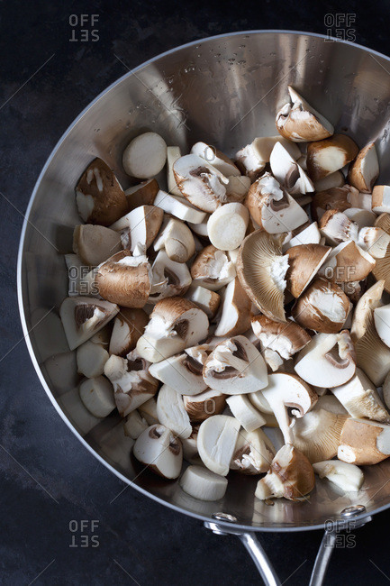 Raw champignons and king trumpet mushrooms in pan