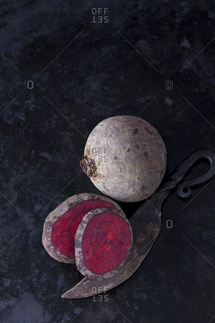 Whole and sliced beetroot and an old knife on dark metal