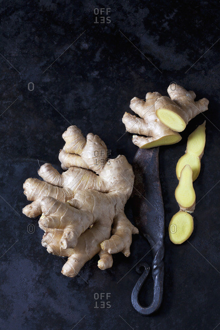 Fresh ginger and an old knife on dark metal