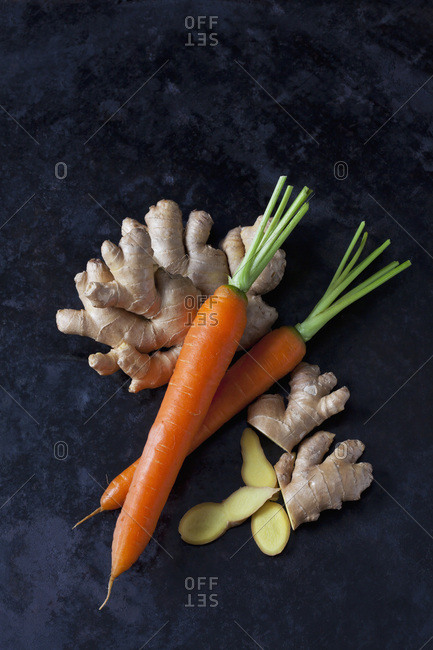 Fresh ginger and carrots on dark metal