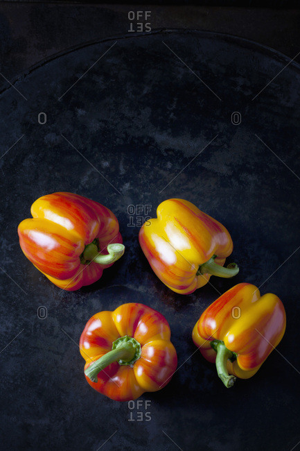 Four tiger bell peppers on dark metal