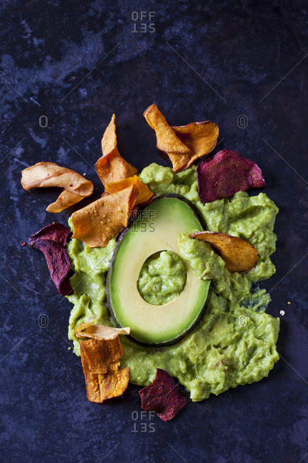 Guacamole- slice of avocado and vegetable chips on dark ground