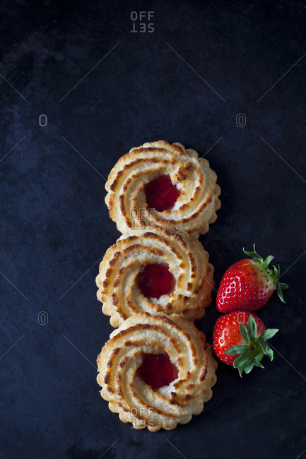 Row of three ox-eye cookies  and two strawberries on dark metal
