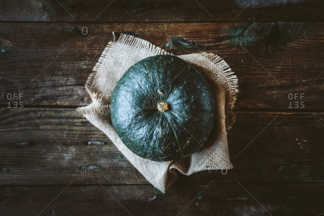 Green pumpkin on jute and dark wood