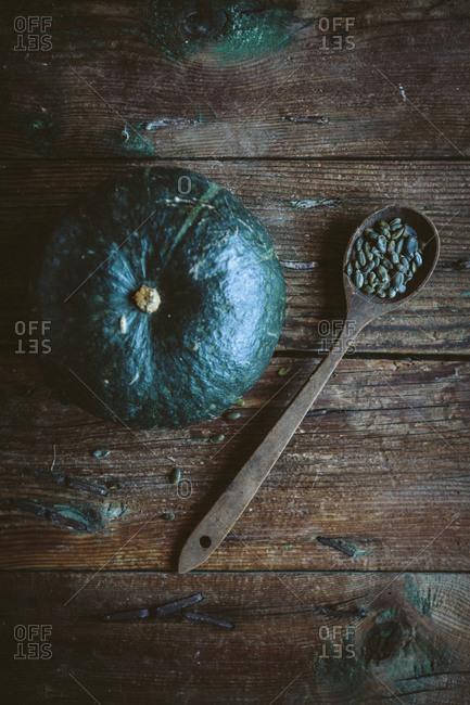 Green pumpkin and spoon of pumpkin seed on dark wood