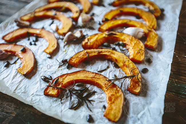 Baked slices of pumpkin- garlic and rosemary on baking paper