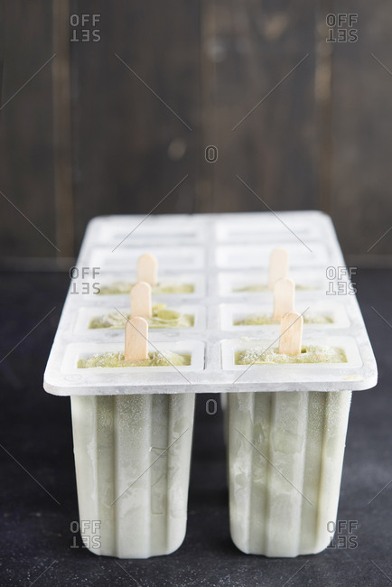 Homemade avocado lime popsicles in plastic box