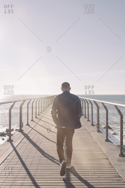 Back view of man walking on boardwalk at backlight