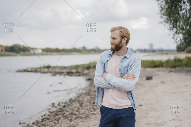 Germany- Dusseldorf- smiling man standing on the beach looking at view