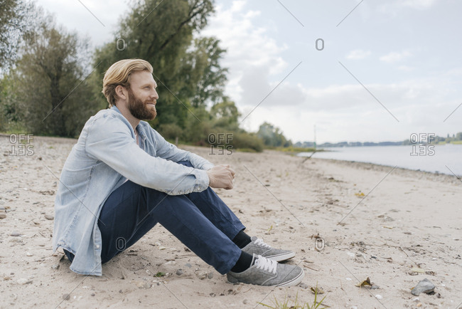 Germany- Dusseldorf- relaxed man sitting on the beach looking at view