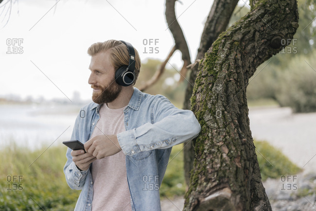 Germany- Dusseldorf- man with smartphone and headphones listening music outdoors
